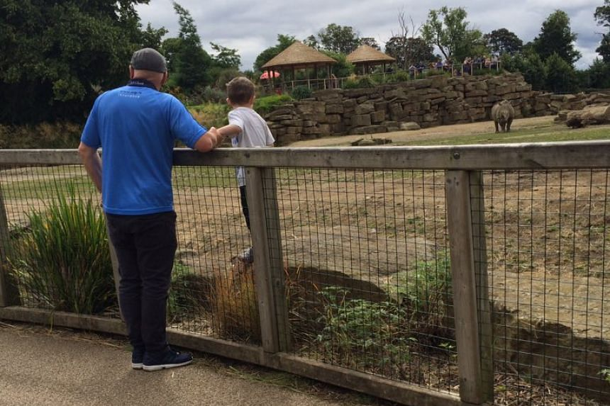 A young boy standing inside a rhinoceros enclosure in the Dublin Zoo on July 30, 2016, accompanied by a male relative.