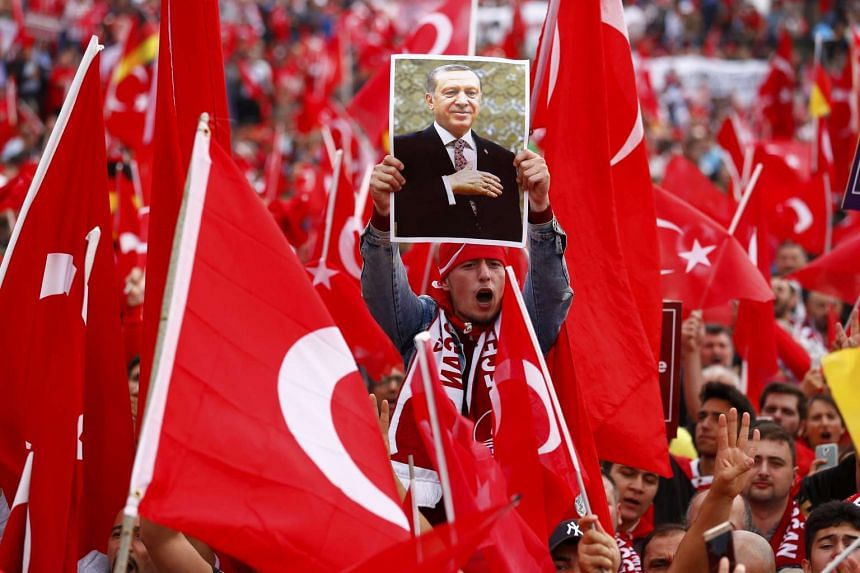 A supporter of Turkish President Tayyip Erdogan holds up a picture during a pro-government protest in Cologne, Germany. Police estimated 40,000 demonstrators had turned up in support of Ergodan.