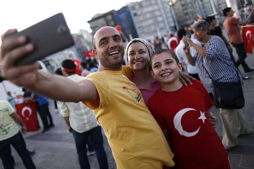 People taking selfies at Taksim Square, in Istanbul, Turkey,  after a failed military coup. Turkey has said it would have to back out of its agreement with the European Union to stem the flow of migrants into the bloc if the EU does not deliver visa-