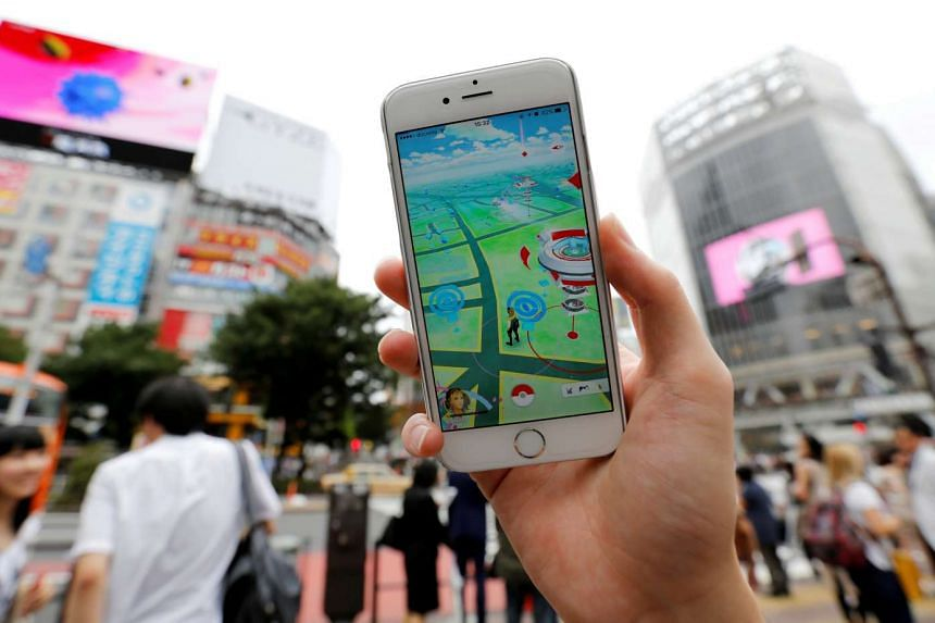 A man poses with his mobile phone displaying the augmented reality mobile game Pokemon Go in front of a busy crossing in Shibuya district in Tokyo. PHOTO: REUTERS