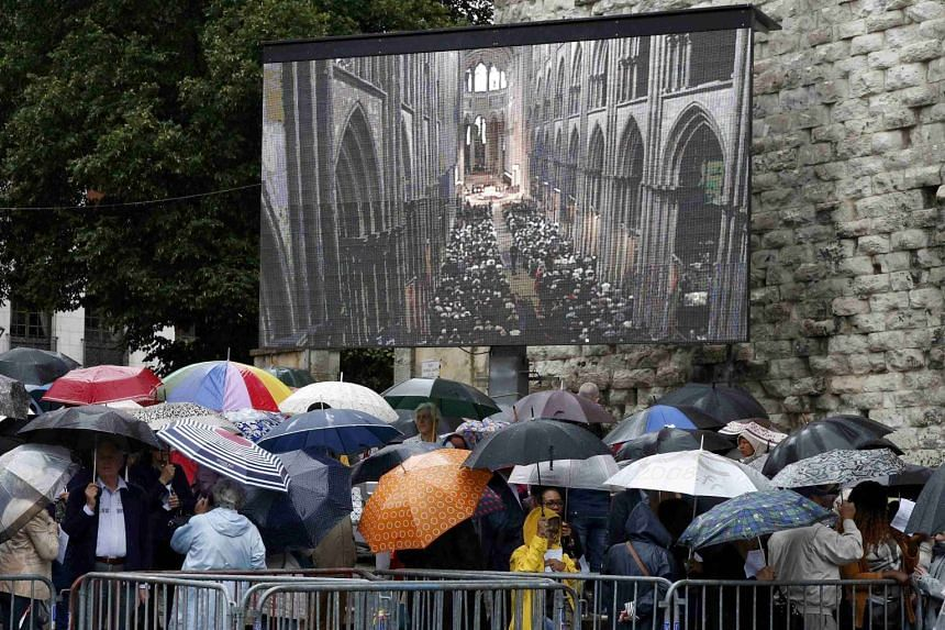 Mourners gathering near a giant screen outside the cathedral in Rouen, France, ahead of a funeral service in memory of slain priest Father Jacques Hamel, on Aug 2, 2016.