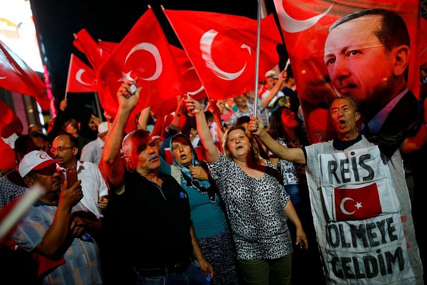 People waving Turkish flags during a demonstration in Ankara on July 27, 2016.