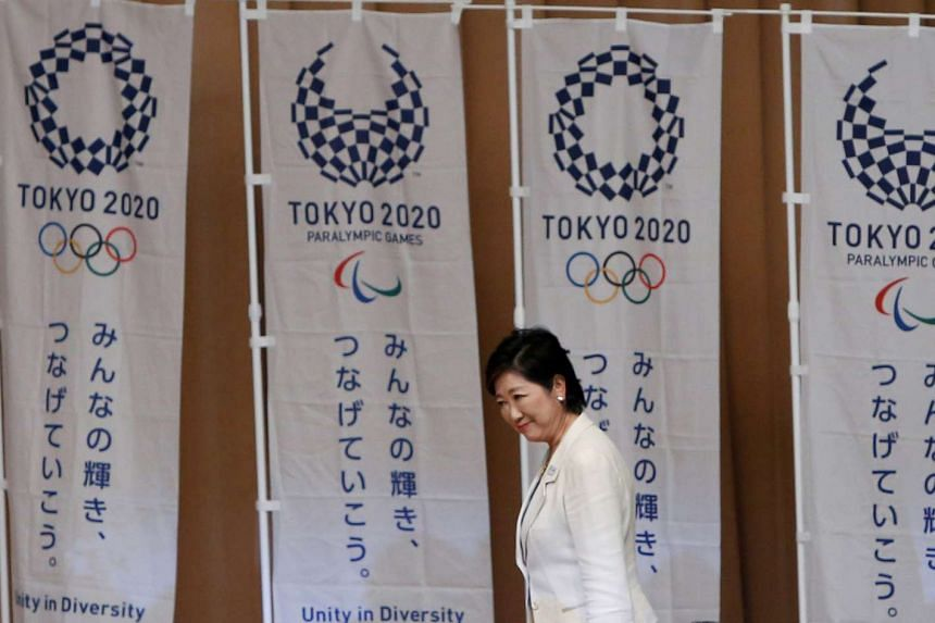 Tokyo Governor Yuriko Koike walking past Tokyo 2020 Olympic and Paralympic Games flags to make a speech at the Tokyo Metropolitan Government Building on Aug 2, 2016.