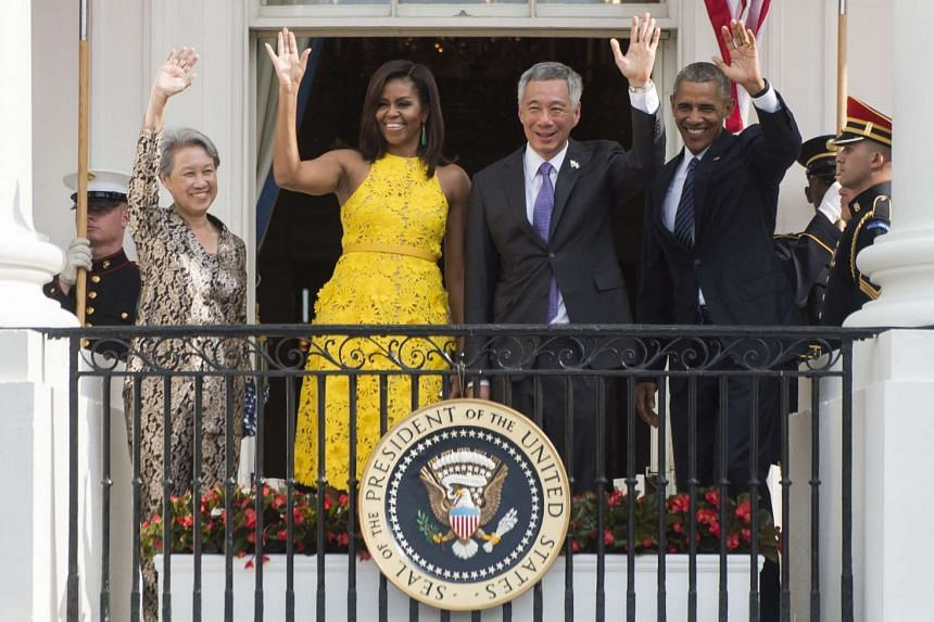 US President Barack Obama (right), First Lady Michelle Obama (second from left), Singapore's Prime Minister Lee Hsien Loong (second from right) and his wife, Mrs Lee, wave during a State Arrival ceremony on the South Lawn of the White House in Washin
