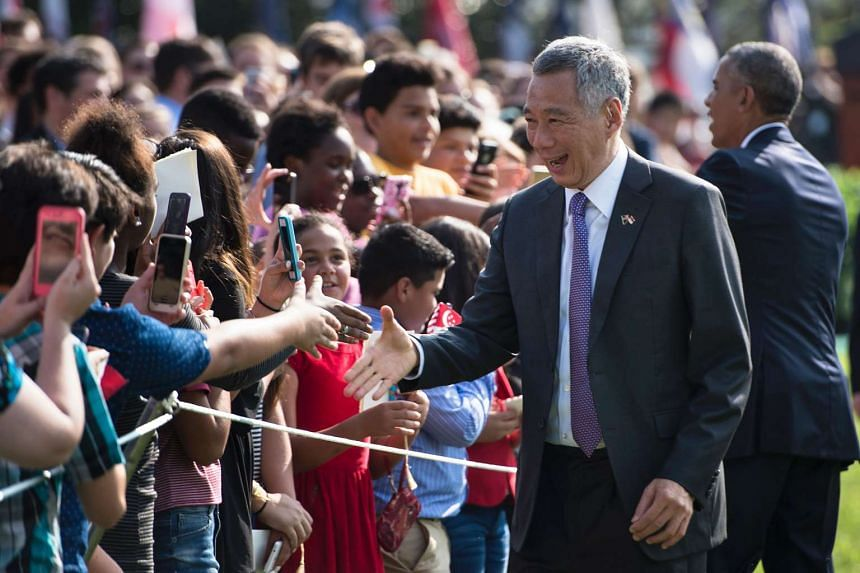 Singapore Prime Minister Lee Hsien Loong (left) and US President Barack Obama greet guests during an arrival ceremony on the South Lawn of the White House August 2, 2016.