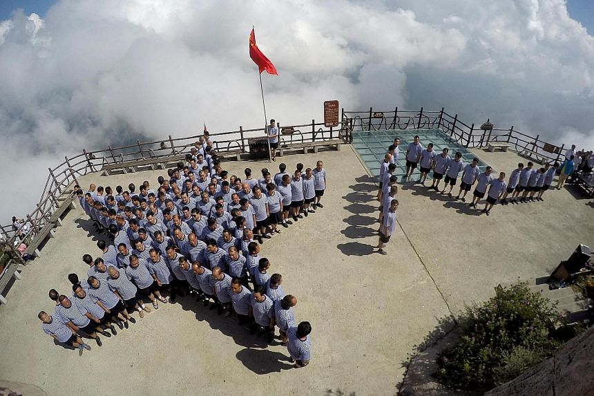 PLA navy veterans standing in formation on Sunday on top of a mountain ahead of China's Army Day in Luoyang, Henan province. President Xi plans to shed 300,000 troops from the 2.3 million-strong military, the centrepiece of China's biggest shake-up o