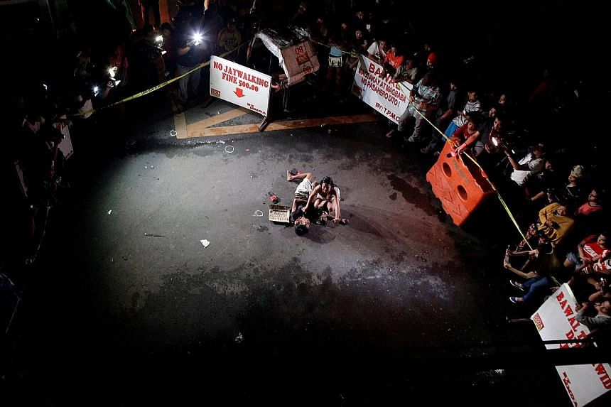 """Ms Olayres weeping over the body of her husband on July 23. He was gunned down by vigilantes, according to police. A cardboard sign found near the body reads: """"Pusher Ako"""", which translates to """"I am a drug pusher."""""""