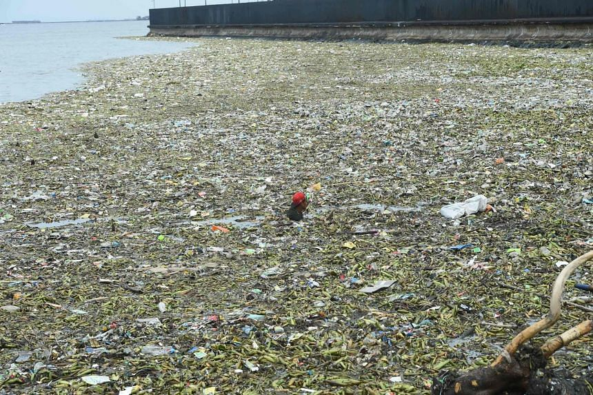 A man looking for recyclable materials among the floating garbage at the Manila Baywalk, washed ashore after Typhoon Nida passed through the northern Philippines yesterday.
