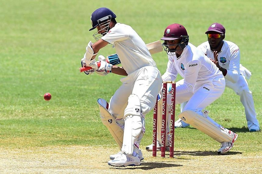 Ajinkya Rahane of India eyes the ball off a delivery from West Indies bowler Devendra Bishoo as wicket keeper Shane Dowrich plays close to the wickets on the third day of their second test cricket match on Aug 1 at Sabina Park in Kingston, Jamaica.