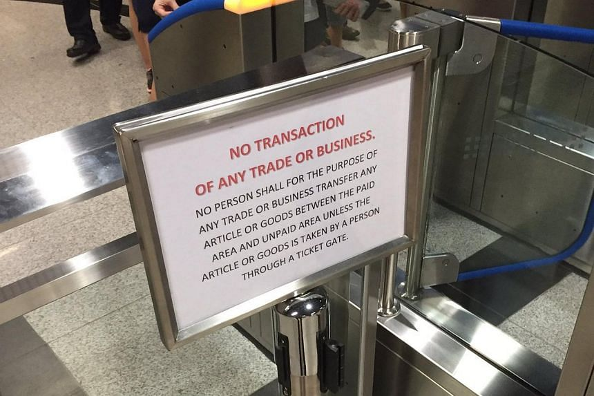 A sign at Beauty World station telling commuters that transactions between the paid and unpaid areas of a train station are not allowed.