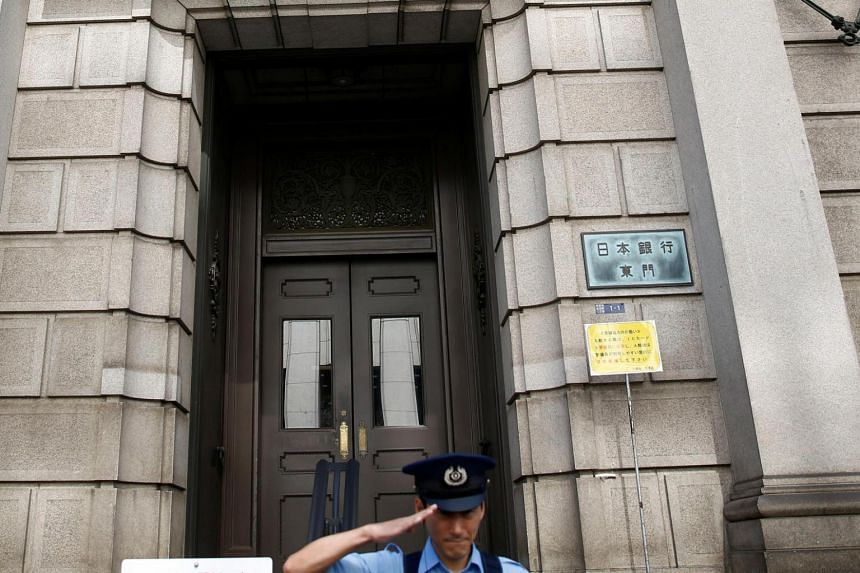 A security guard salutes in front of the Bank of Japan building in Tokyo, Japan, July 29.
