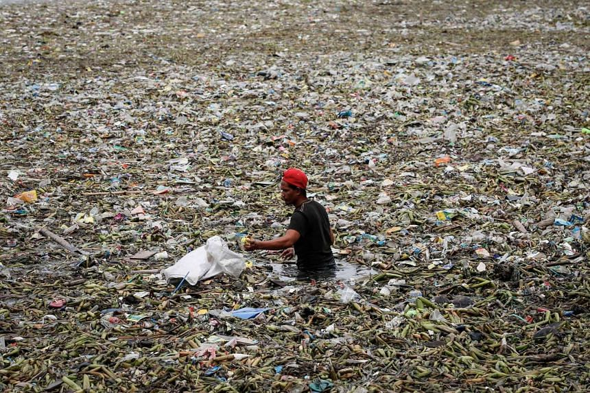 A Filipino removes rubbish brought by strong waves from Typhoon Nida along the Manila Bay, Manila, Philippines, Aug 1.