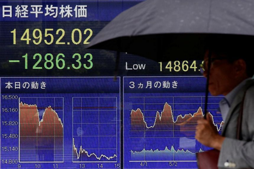 A man walks past a screen displaying the Nikkei average outside a brokerage in Tokyo, Japan, on June 24.