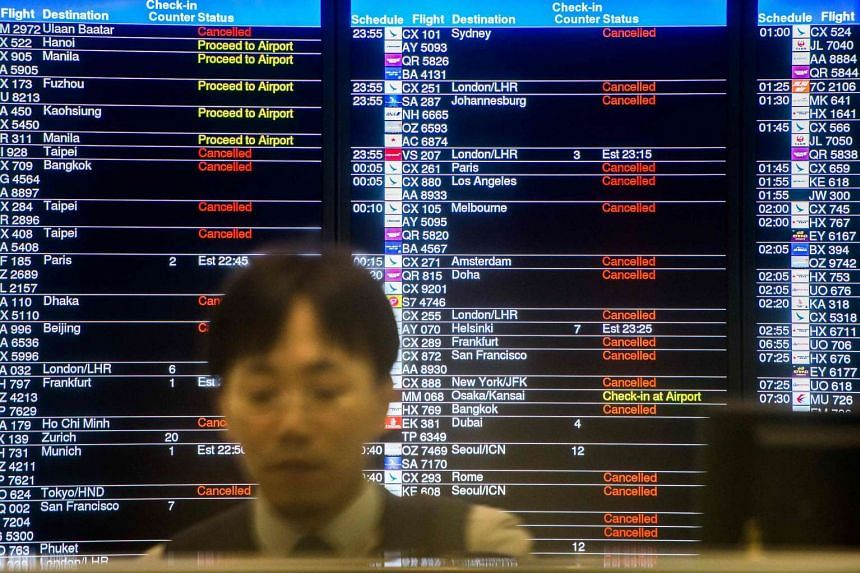 A member of staff at the Airport Express terminal sits in front of an information board displaying a list of cancelled and delayed flights in Hong Kong.