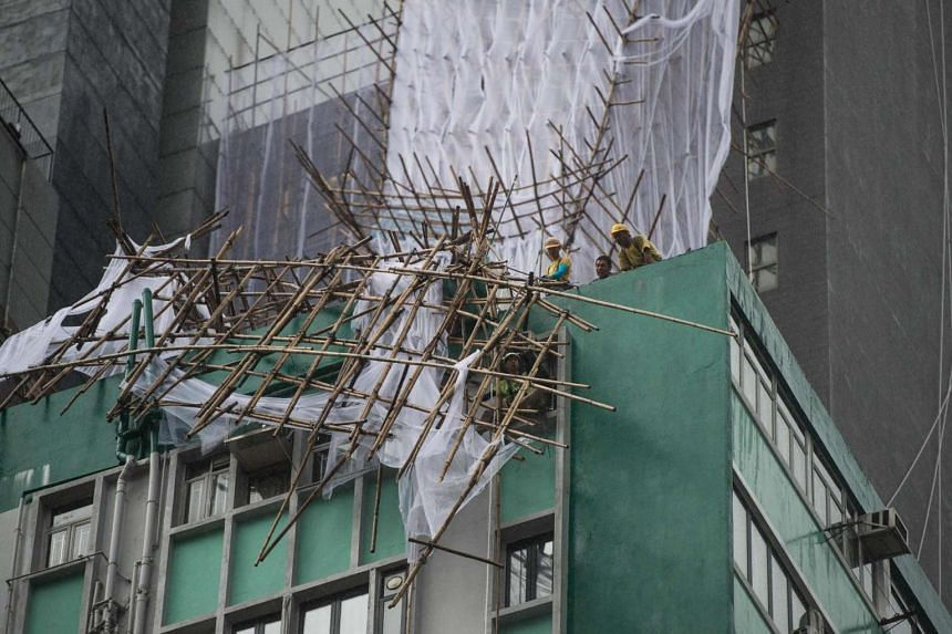 "Rescue workers attempt to secure bamboo scaffolding that was damaged overnight at the top of a building in Hong Kong on Aug 2, during a ""T8"" storm signal raised for Typhoon Nida."