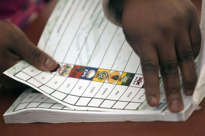 An Election Commission worker tearing a ballot paper at a voting station in Johannesburg on Aug 3, 2016.