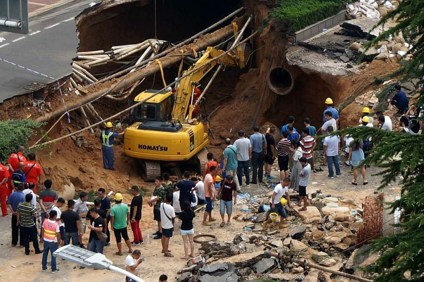 Rescuers searching for missing people after a giant sinkhole opened up on a road in Zhengzhou, in central China's Henan province, on Aug 2, 2016.