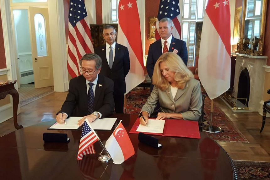 David Koh and Suzanne Spaulding sign the MoU, watched by Singapore ambassador to the US Ashok Mirpuri (standing, left) and US ambassador to Singapore Kirk Wagar.