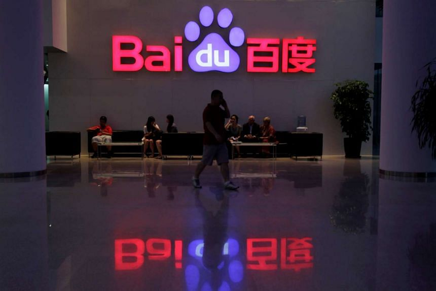 A employee uses his mobile phone as he walks past the Baidu headquarters in Beijing.