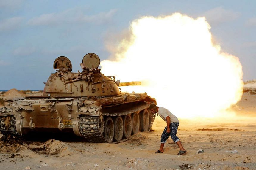 A fighter of Libyan forces allied with the UN-backed government fires a shell with Soviet made T-55 tank at Islamic State fighters in Sirte, Libya, on Aug 2, 2016.