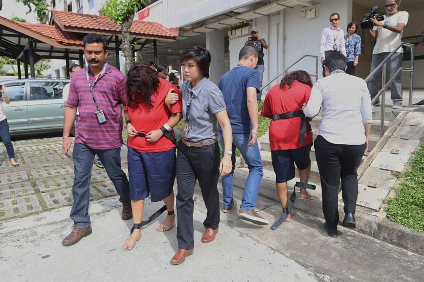 Gaiyathiri Murugayan (left, in red) and her mother Prema Naraynasamy (right, in red), were taken back to their home by police for investigations on Aug 3, 2016.