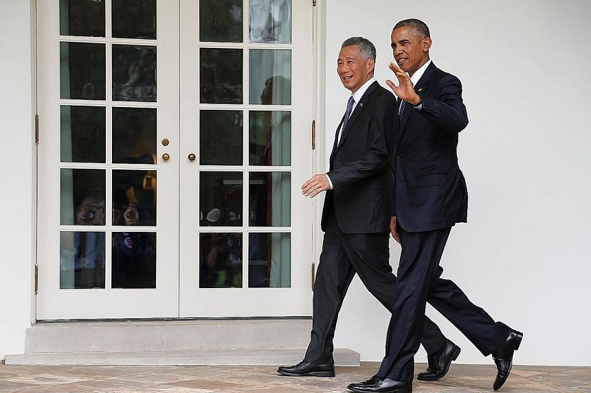 Clockwise from right: PM Lee and Mr Obama chatting in the Oval Office yesterday, acknowledging the crowd as they walked to their meeting at the White House, and taking the stage during the state arrival ceremony on the South Lawn yesterday. Some 2,00