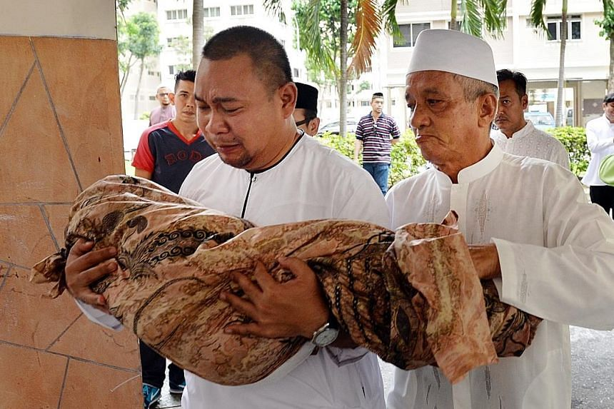 Mr Syahrom Mohammad Yunus carrying the body of his daughter for burial on Feb 14. Three-year-old Nur died of pneumonia following the traumatic injury to her head in the fall.