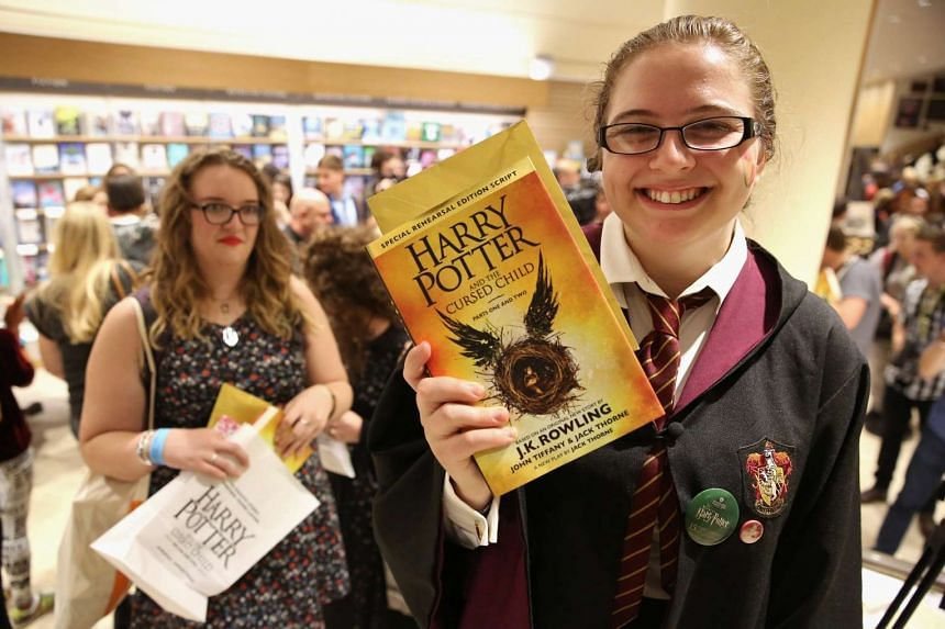 A woman holds copies of Harry Potter And The Cursed Child at a bookstore in London, Britain, July 31, 2016.