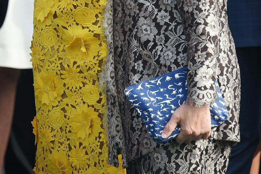 Mrs Lee Hsien Loong holding a pouch called the Denim Pouch-Dino Blue Black during the welcome ceremony at the White House on Aug 2, 2016. The pouch was designed by Pathlight student See Toh Sheng Jie.