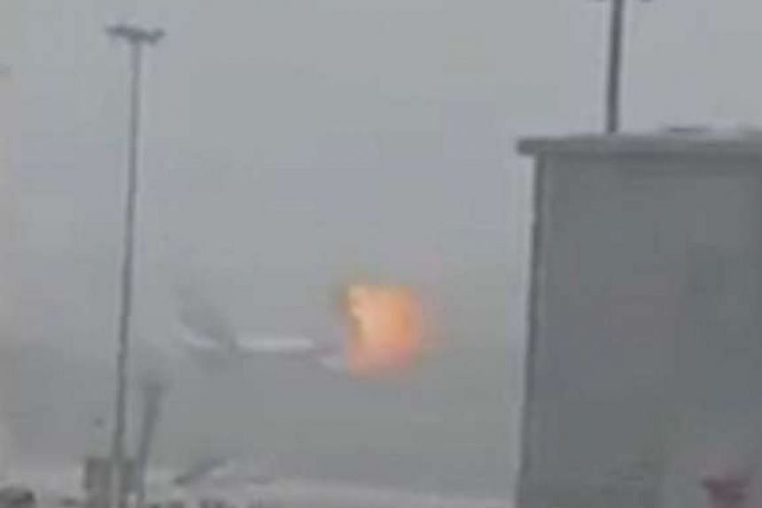 An image taken from an amateur video shows the moment an explosion occurs on an Emirates Airline airplane at Dubai airport.