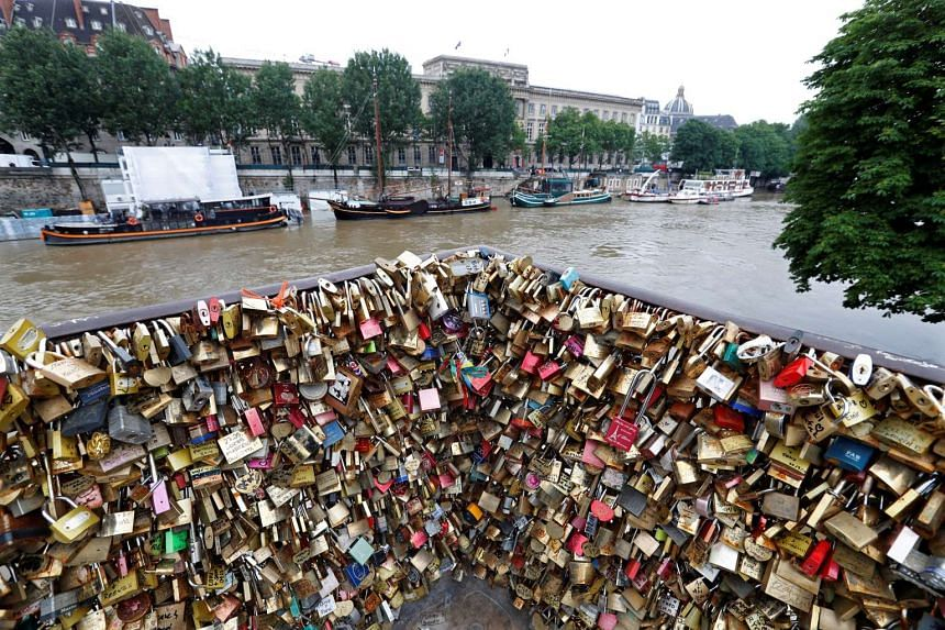 Padlocks clipped on by lovers are seen in front of the flooded river-side of the River Seine in Paris, France, June 1, 2016.