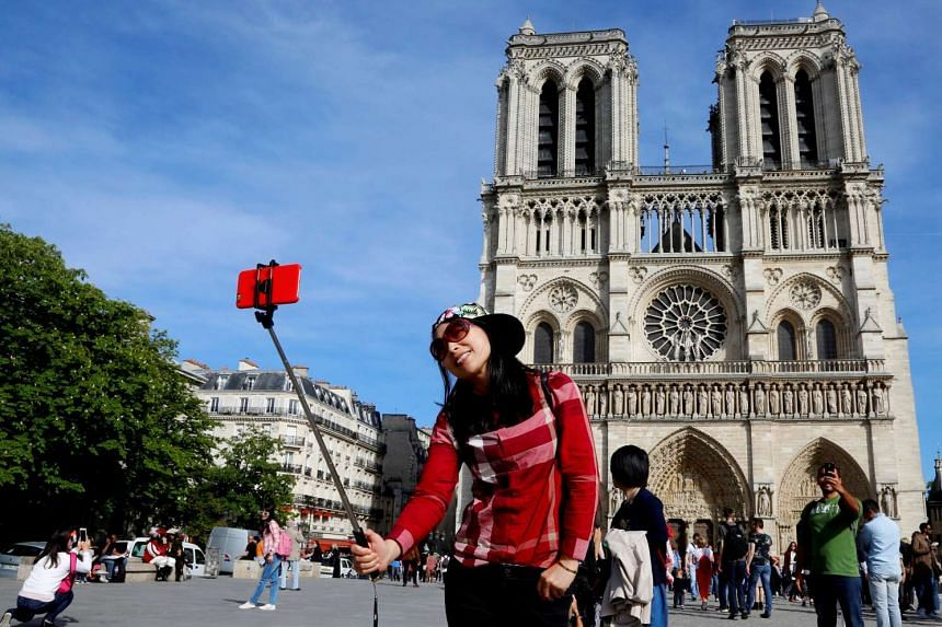 A Chinese tourist takes a selfie in front of the Notre Dame Cathedral in Paris, France, May 5, 2016.