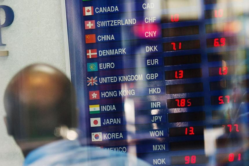 A man looks at global rates at a currency exchange shop in Times Square on June 24, 2016 in New York.