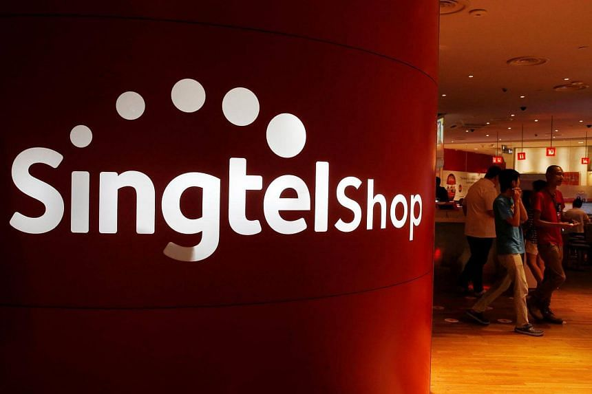 Customers walk out of a Singtel shop at a mall in Singapore on May 11, 2016.