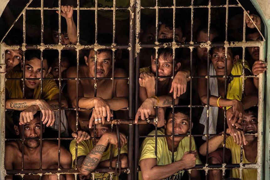 Inmates peeking from their cell inside the Quezon City Jail in Manila.