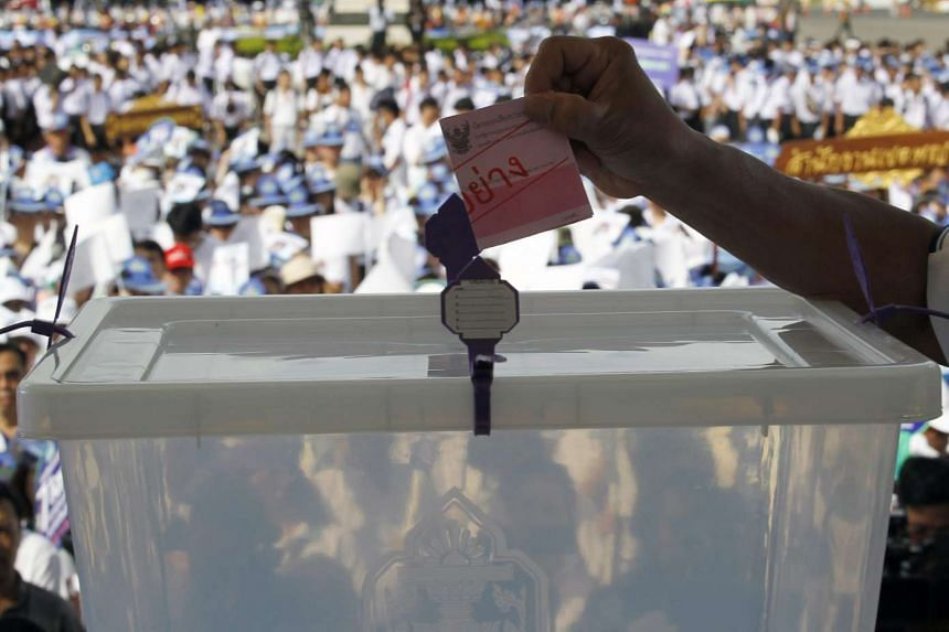 A Thai Election Commission's official cast an example ballot at a campaign to promote the referendum on a new constitution in Bangkok, on Aug 4, 2016.