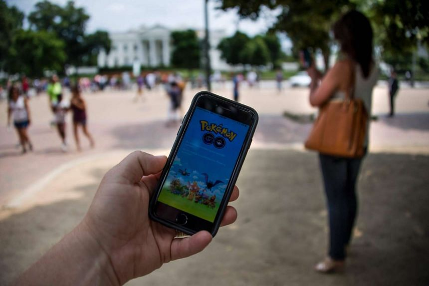 A man holds up his cell phone with a screen shot of the Pokemon Go game in front of the White House in Washington, DC, on July 12, 2016.