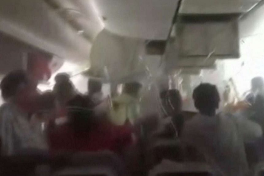 A screengrab from a video shows passengers in an Emirates Airline airplane trying to access oxygen masks, after the plane crash-landed and seconds before the fuselage was engulfed in a ball of flame, on Aug 3, 2016.