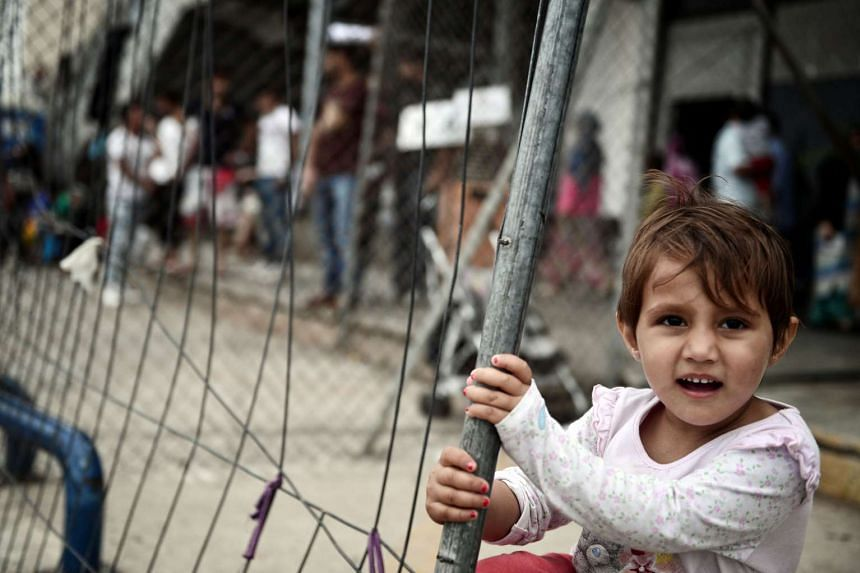 A child plays in a camp at the arrivals area of the old Athens airport on June 13, 2016.