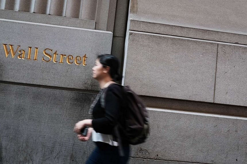People walk by the New York Stock Exchange (NYSE) on Wall Street.