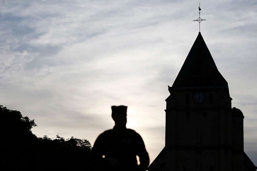 A Police officer stands guard at the Saint-Etienne church in Saint-Etienne-du-Rouvray.