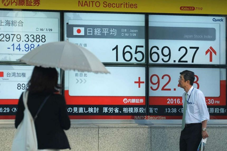 Pedestrians walk in front of an electric quotation board displaying the Nikkei key index of the Tokyo Stock Exchange in Tokyo on July 29, 2016.