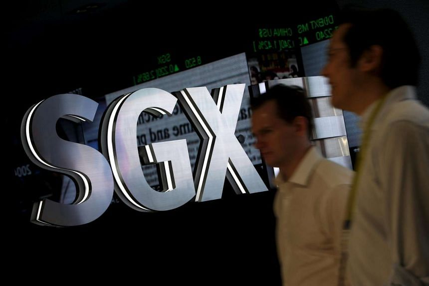 People walking past a Singapore Exchange logo at their head office in Singapore on April 22, 2015.