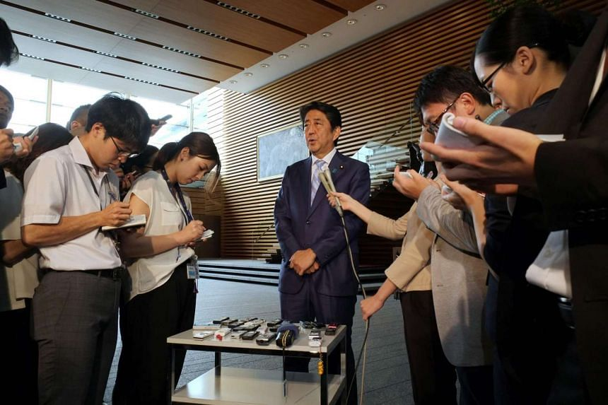 Japan's Prime Minister Shinzo Abe (centre) speaks to reporters at his official residence in Tokyo on August 3, 2016, following a ballistic missile launch by North Korea.
