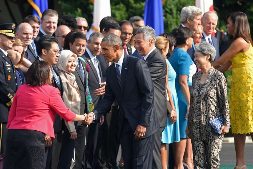 Mr Obama shakes hands with Ms Chang Li Lin, Press Secretary to Prime Minister Lee.