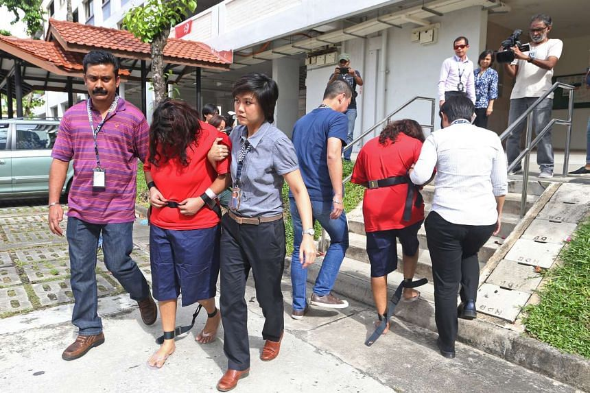 Police officers escorting Gaiyathiri Murugayan (left, in red) and Prema Naraynasamy (right, in red) during investigations, on Aug 3, 2016.