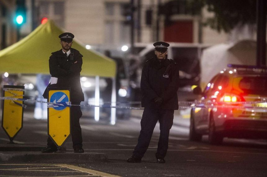 Police officers guard the scene where one women died and several were injured in a suspected knife attack in Russell Square, Central London, Aug 4.