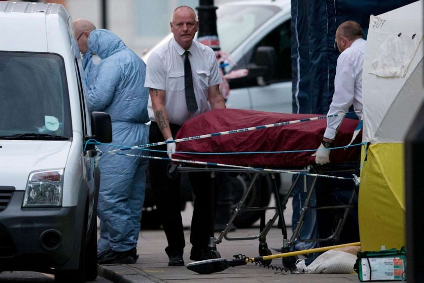 A private ambulance crew remove a body from Russell Square in London early on Aug 4 after a woman in her 60s was killed.