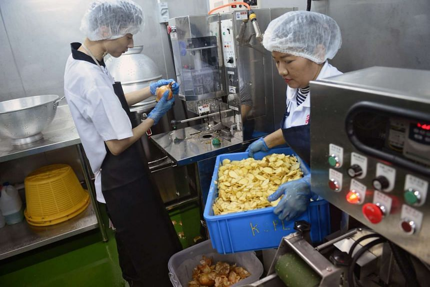 An employee operates an onion peeler machine (left) as another carries a box full of sliced ginger at Kitchen Solutions on Aug 4, 2016.