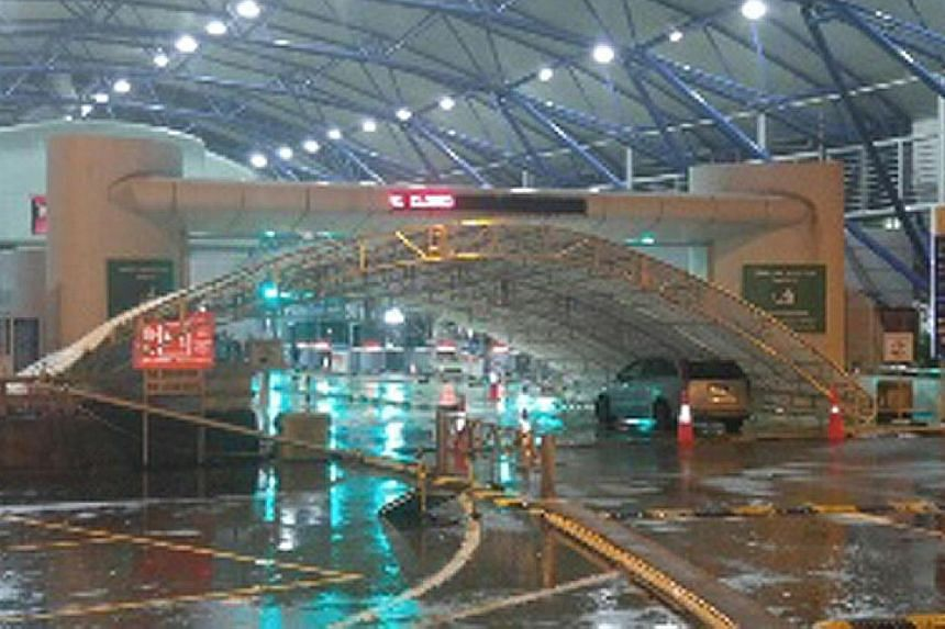 Above: The fallen canopy at the Tuas Checkpoint's car arrival lane yesterday morning. Some cars had to be diverted. Left: Motorcyclists at the motorcycle arrival lane, where another canopy had been brought down by strong wind and heavy rain. Operatio